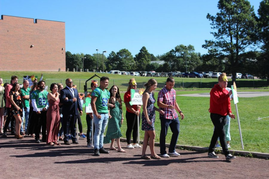 Homecoming Court and their teacher escorts walking out at the assembly.