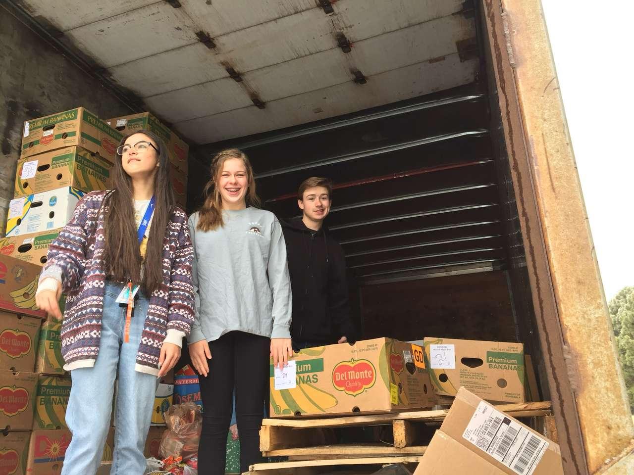 Michael Kirkpatrick, Catie Taylor, and Koki Davis load donated food into the Harvest of Love semi-truck.