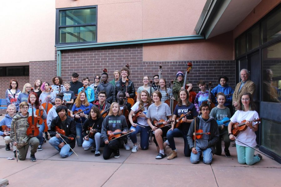 Doherty's orchestra poses for a picture with conductor Mr. Bowen.