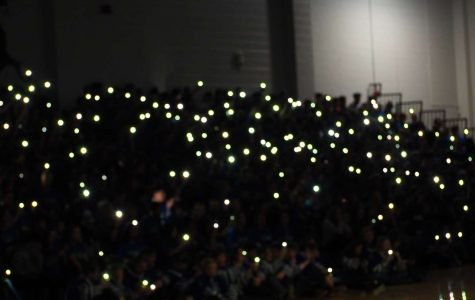 Students with their phone flashlights as the lights are dimmed for the cheer