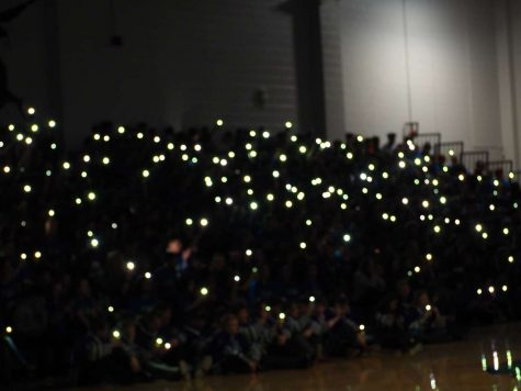 "Students with their phone flashlights as the lights are dimmed for the cheer ""Rollercoaster."""