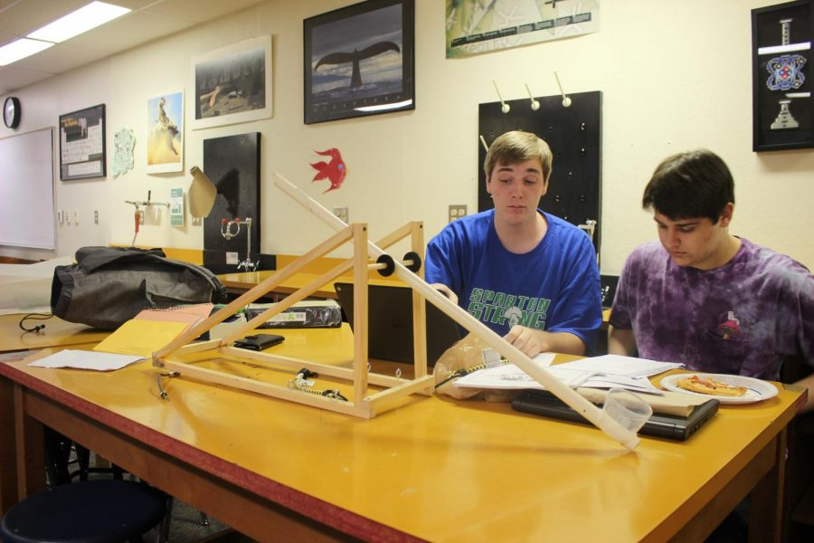 Jack Bopp and his partner modify their catapult project.