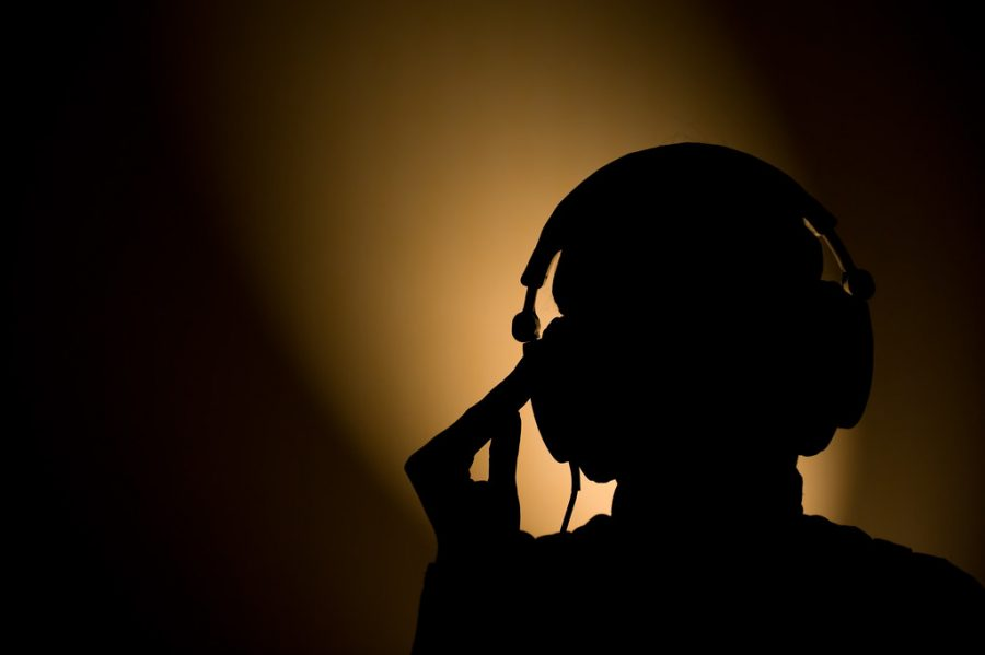 A silhouette slides headphones on by computer light.